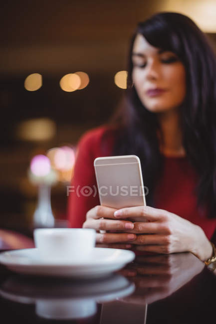 Frau benutzt Handy in Restaurant — Stockfoto