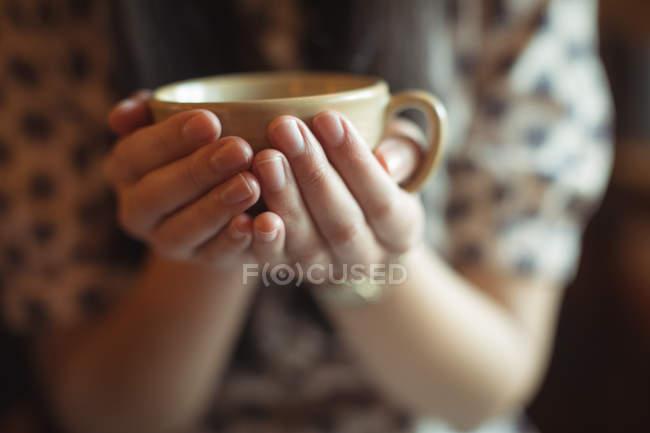 Розділ середині Жінка тримає чашку кави в кафе — стокове фото