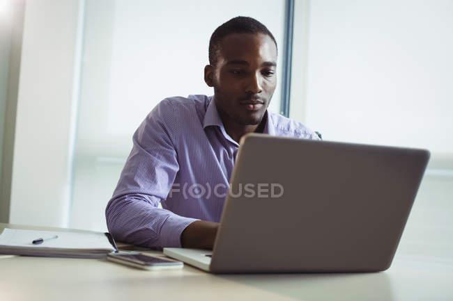 Dirigeant d'entreprise utilisant un ordinateur portable au bureau — Photo de stock