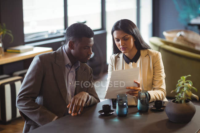 Businessman and a colleague discussing over document in office — Stock Photo