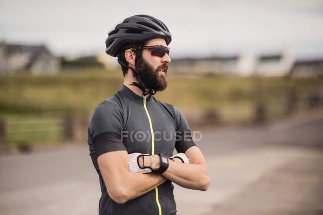 Спортсмен, стоя с руками, скрещенными на дороге — стоковое фото