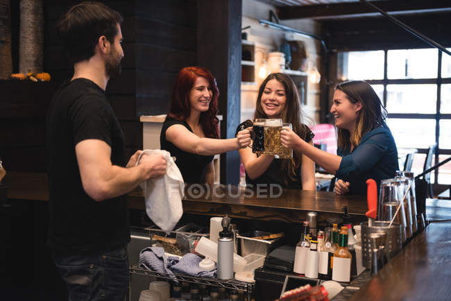 Happy friends toasting with beer glasses at bar counter — Stock Photo