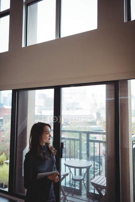 Женщина держит цифровой планшет, глядя в окно дома — стоковое фото