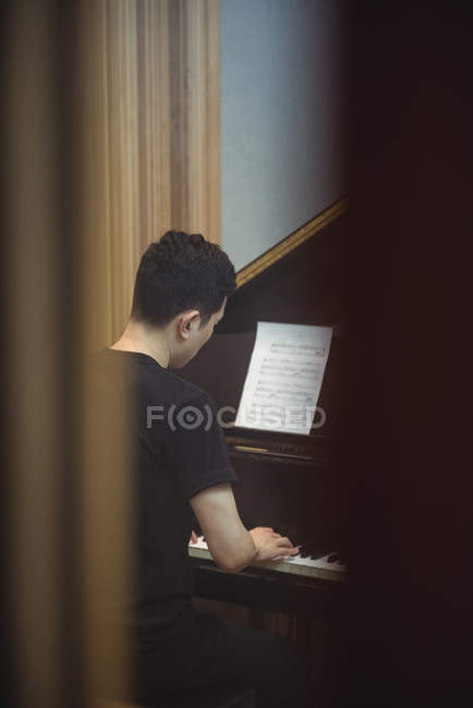 Rear view of man playing a piano in music studio — Stock Photo