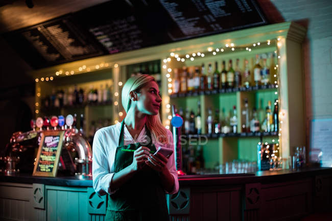 Smiling waitress writing down the order in the bar — Stock Photo