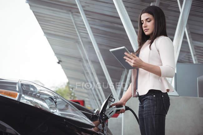 Belle femme à l'aide de tablette numérique tout en chargeant la voiture électrique à charge conductive pour véhicules — Photo de stock