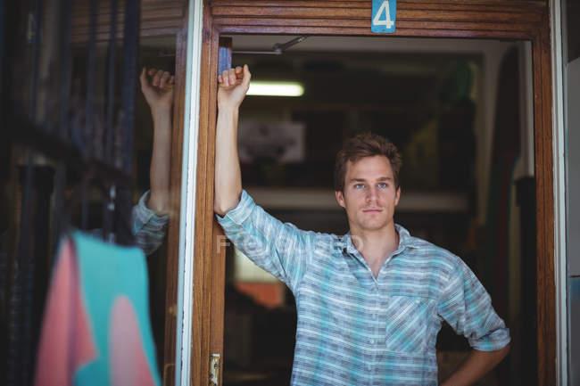 Вдумчивый человек стоит перед входом в магазин — стоковое фото
