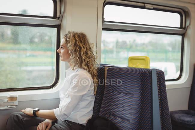 Вид збоку бізнес-леді дивлячись через вікно під час подорожі — стокове фото