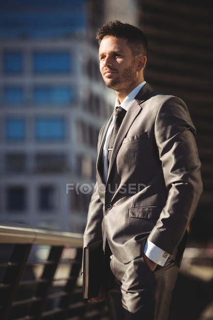 Businessman with a diary standing at office terrace in daylight — Stock Photo