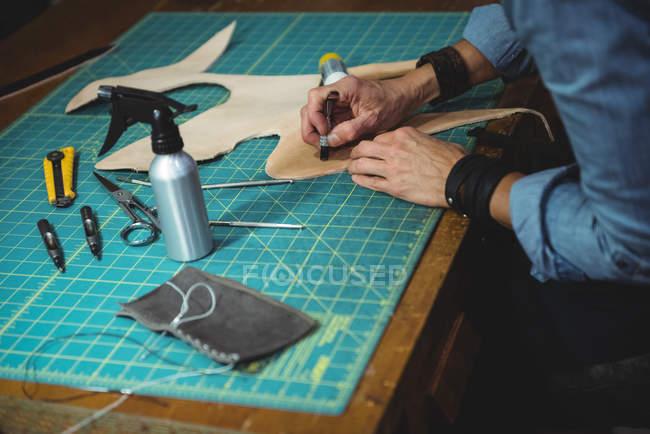 Середньої частини craftswoman працює над шматок шкіри в майстерні — стокове фото
