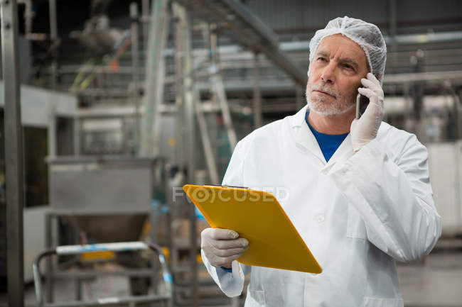 Serious male worker talking on mobile phone in cold drink factory — Stock Photo