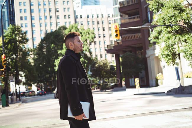 Uomo d'affari con tablet digitale che attraversa la strada di giorno — Foto stock