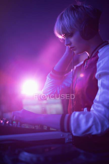 Dj femenino escuchando auriculares mientras reproduce música en el bar - foto de stock