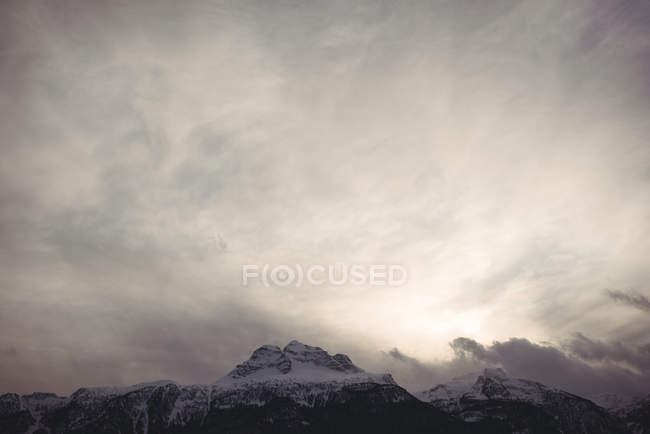 Scenic view of snowcapped mountains against cloudy sky — Stock Photo