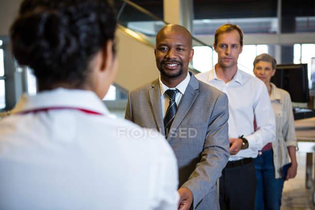 Geschäftsmann übergibt Bordkarte an weibliches Personal im Flughafen-Terminal — Stockfoto