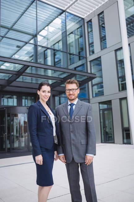 Portrait d'homme d'affaires confiant avec collègue debout extérieur immeuble de bureaux — Photo de stock