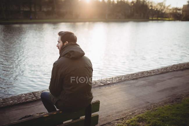 Jovem atencioso sentado no banco perto da ribeira — Fotografia de Stock