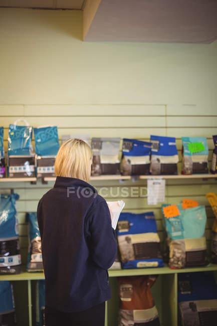 Mulher escrevendo no bloco de notas em loja no centro de cuidado do cão — Fotografia de Stock