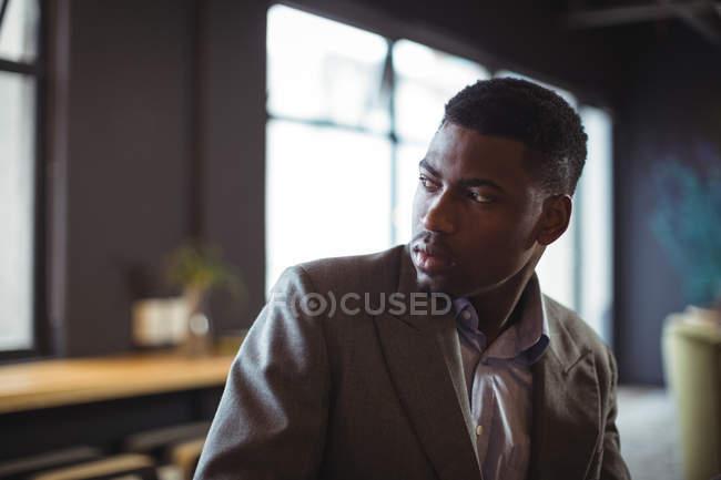 Продуманий бізнесмен фотографіях хтось дивитися вбік в офісі — стокове фото