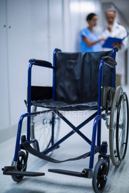 Empty wheelchair in hospital corridor with doctors talking in background — Stock Photo