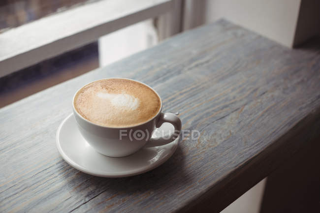 Close-up of cup of coffee on wooden table — Stock Photo