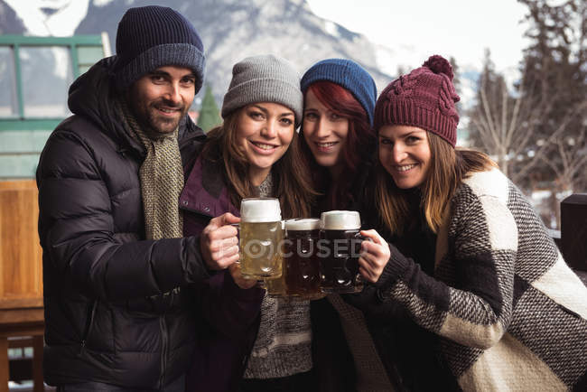 Portrait of happy friends toasting with beer glasses in outdoor terrace — Stock Photo