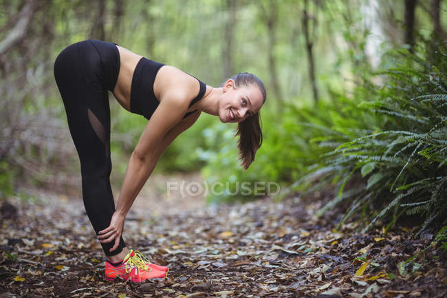 Smiling woman performing stretching exercise in forest — Stock Photo