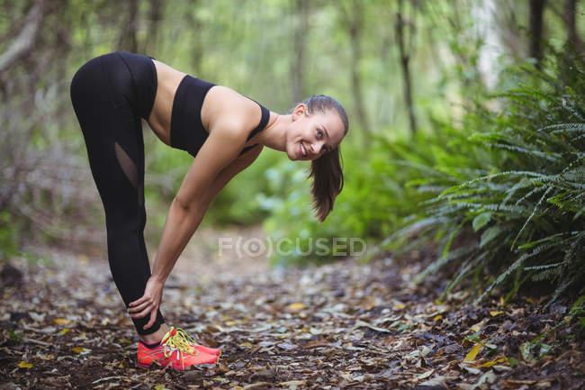 Lächelnde Frau, die Durchführung von stretching-Übung im Wald — Stockfoto