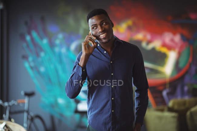 Бизнесмен разговаривает по телефону в офисе — стоковое фото
