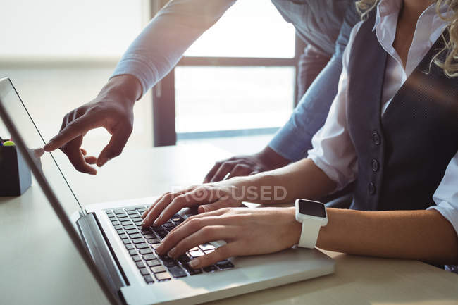 Close-up of business executives discussing over laptop in office — Stock Photo