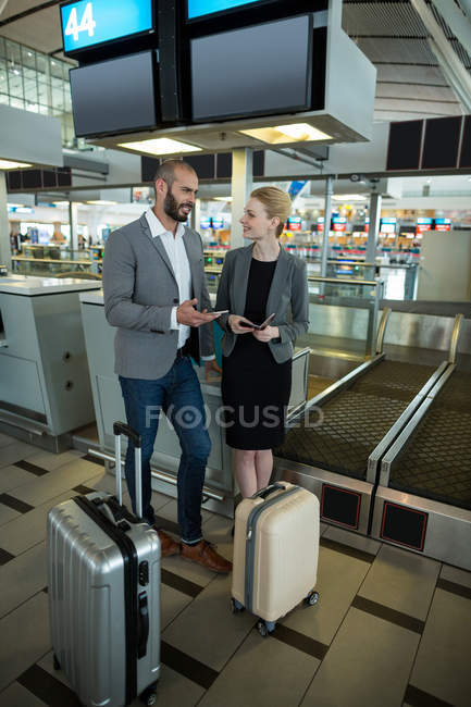 Business people holding boarding pass and using mobile phone in airport terminal — Stock Photo
