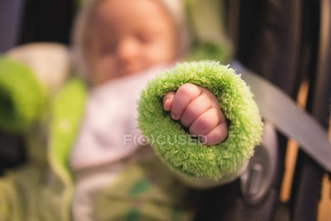 Close-up of baby hand in green baby clothing indoors — Stock Photo