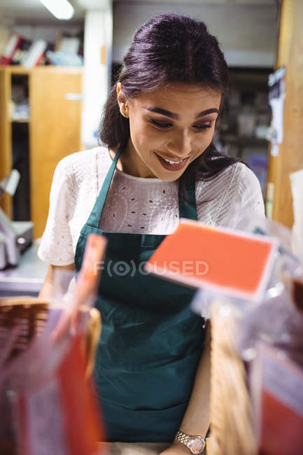 Female staff working at food counter in supermarket — Stock Photo