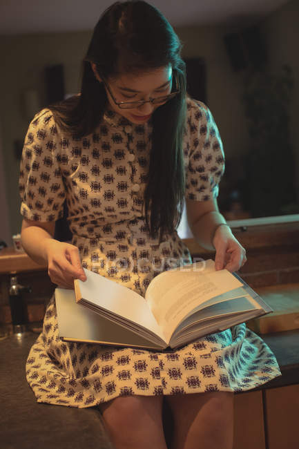 Woman sitting and reading a book at home — Stock Photo