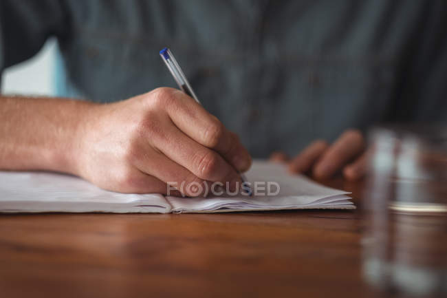 Close-up of man writing on notebook — Stock Photo