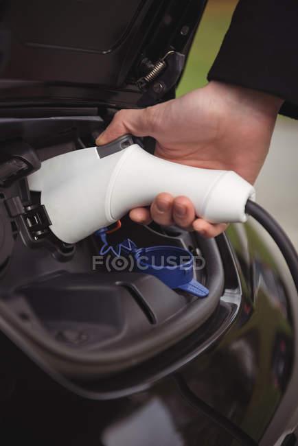 Homme recharge voiture électrique à la station de recharge de véhicule électrique — Photo de stock