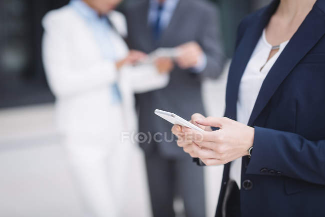 Mid section of a businesswoman using on mobile phone — Stock Photo