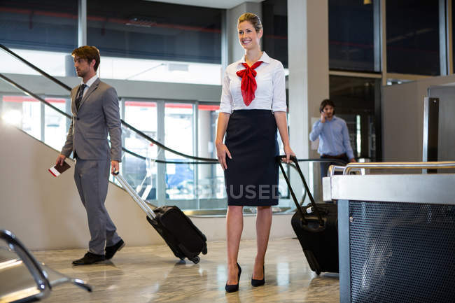 Businessmen and female staff walking with luggage in waiting area at airport — Stock Photo