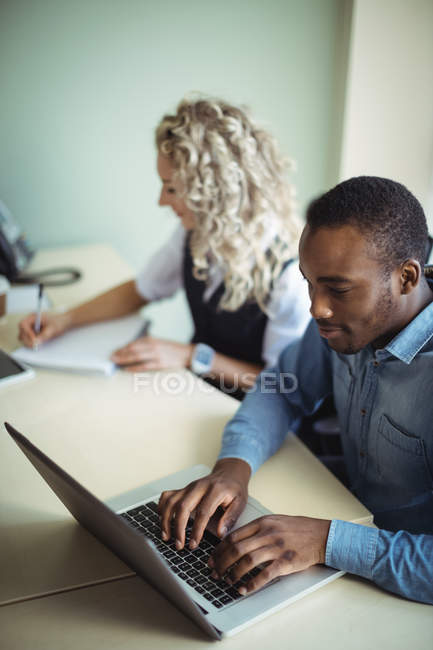 Business executives using laptop in office — Stock Photo