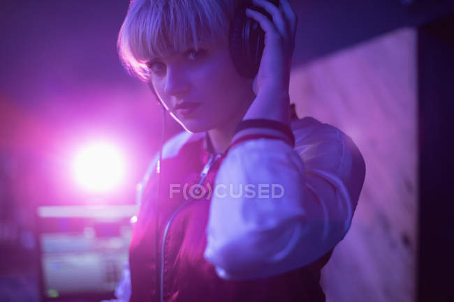 Portrait of female dj listening to music in headphones at bar — Stock Photo