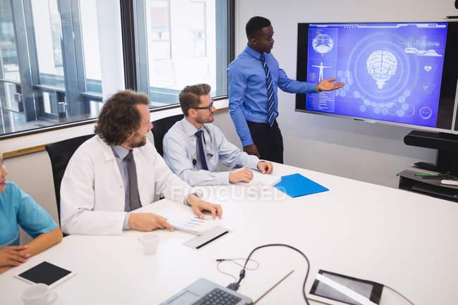 Arzt stellt Team von Interimsärzten im Konferenzraum vor — Stockfoto