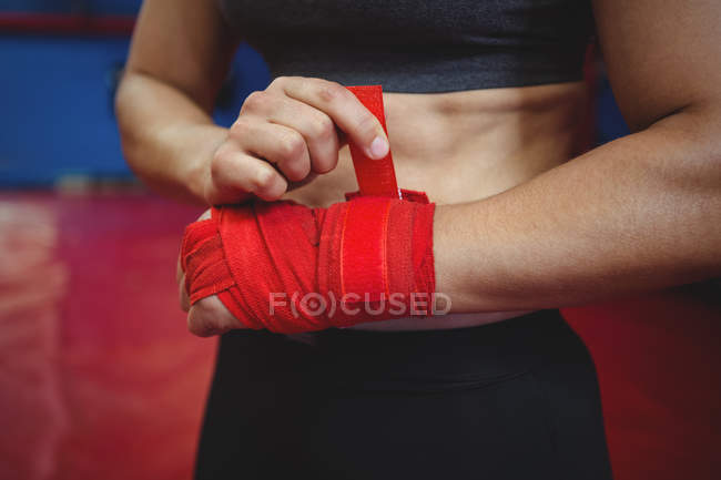 Mid section of female boxer wearing red strap on wrist in fitness studio — Stock Photo