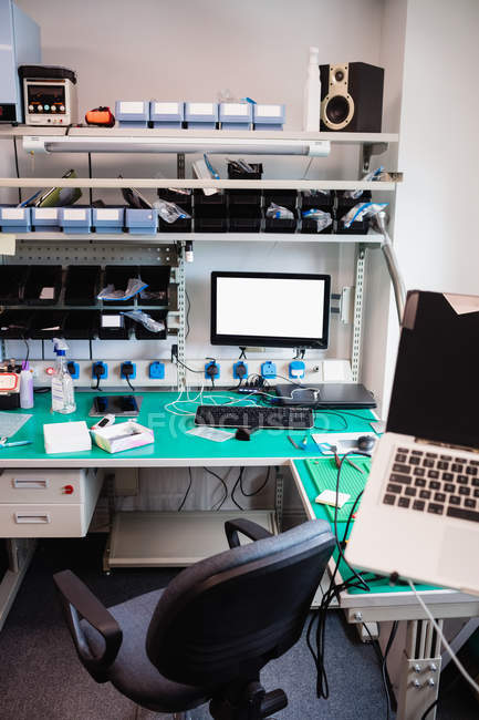 Стол с различным оборудованием в центре ремонт электроники — стоковое фото