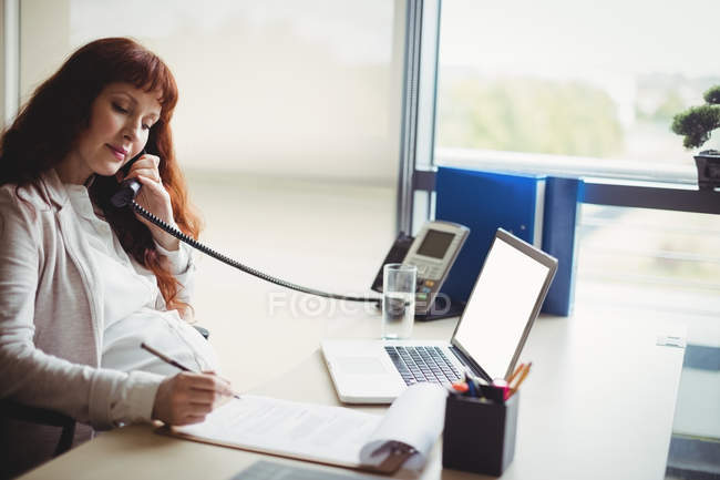 Pregnant businesswoman talking on telephone while working in office — Stock Photo