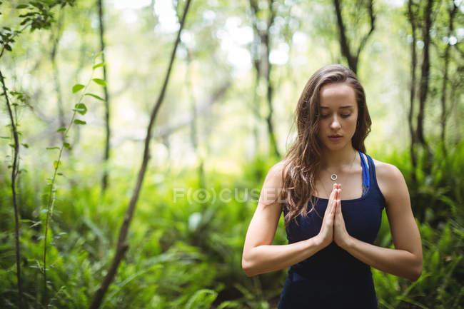 Femme effectuant du yoga en forêt par une journée ensoleillée — Photo de stock