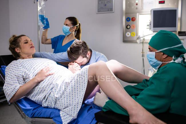 Arzt untersucht Schwangere während der Entbindung, während Mann ihre Hand im Operationssaal hält — Stockfoto