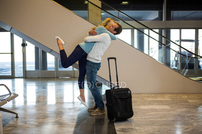 Happy couple embracing each other at the airport — Stock Photo