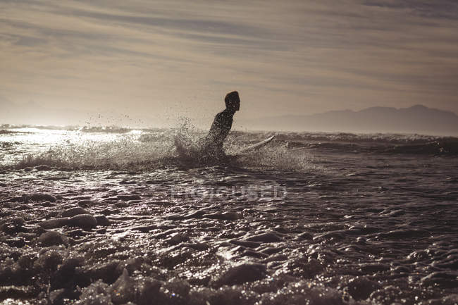 Silhouette of man surfing at dusk in sea water — Stock Photo