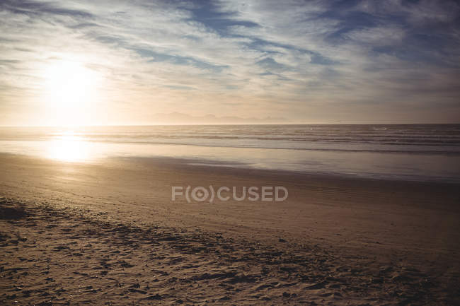 Tranquil view of beach with cloudy sky and bright sun — Stock Photo