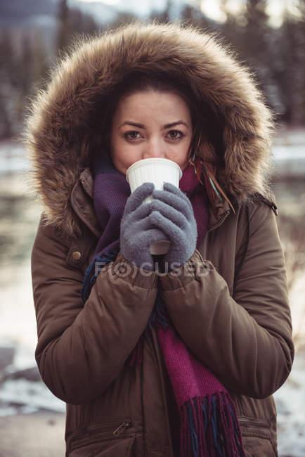 Ritratto di bella donna in cappotto di pelliccia bere caffè in inverno — Foto stock